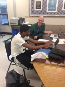 Mr. Frazier helps student on an essay in room D101