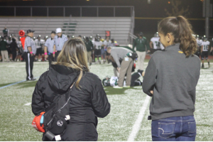 Ms. Sam Keeler (left) stands on the sideline during a 2014 football game (file photo)
