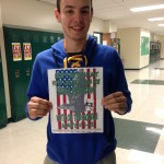 Jacob Reese, who is running for 2016-2017 STUCO president, stands in the hallway with one of his campaign posters.