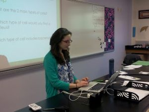 Ms. Amanda Corrado works on her computer at her desk during a presentation in her classroom.