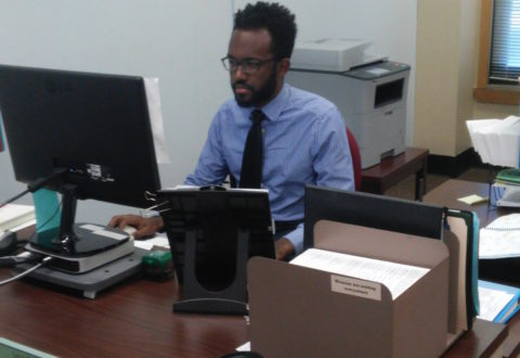 Mr. Leon Douglas sits at his desk in Ms. Odetta Smith's office in the H-wing.