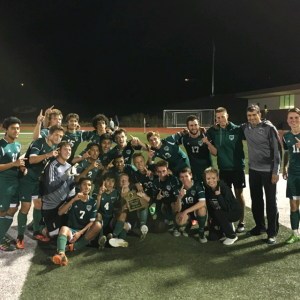 The varsity boy's soccer team takes a picture with the district trophy after winning the game 1-0. (Submitted photo)