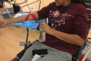 Senior, Roma Patel, drinking water after giving blood