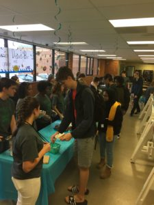 Students are in line to get one dessert. They got to choose from cheesecake or cupcakes.