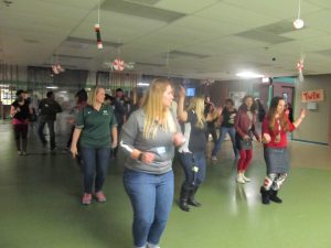 Students and teachers dance together in the cafeteria during the 'Night to Shine' event.