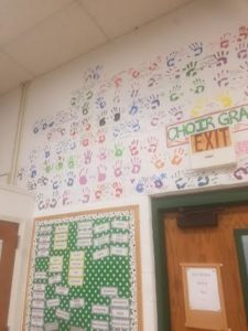 Choir students put their handprints on the wall on last day