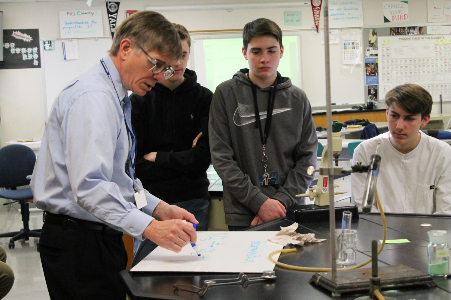 Mr. Ken Smith works with students on a science project during class.