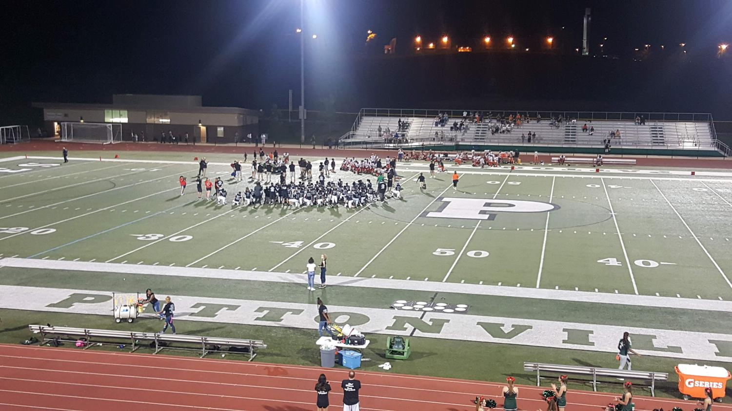 The Pattonville and Webster Groves football teams kneel in respect for the injured player as he is being treated on the field.