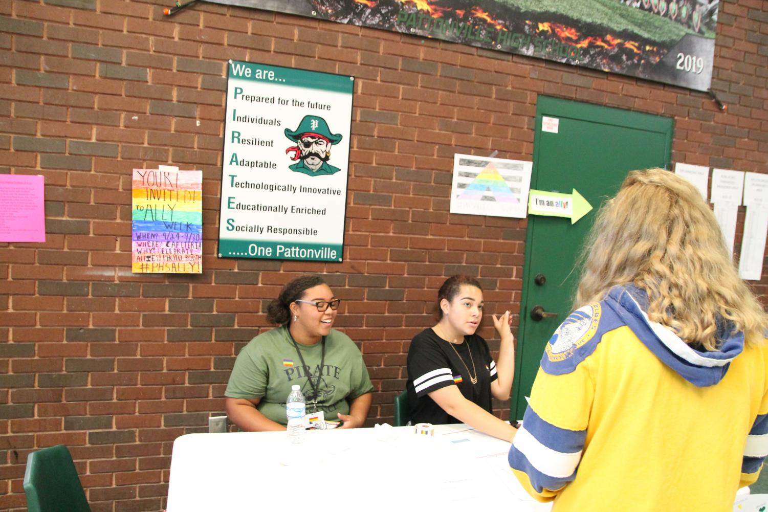Summer Davis (left) and Haley Cooper (right) talk to a student about Ally Week.