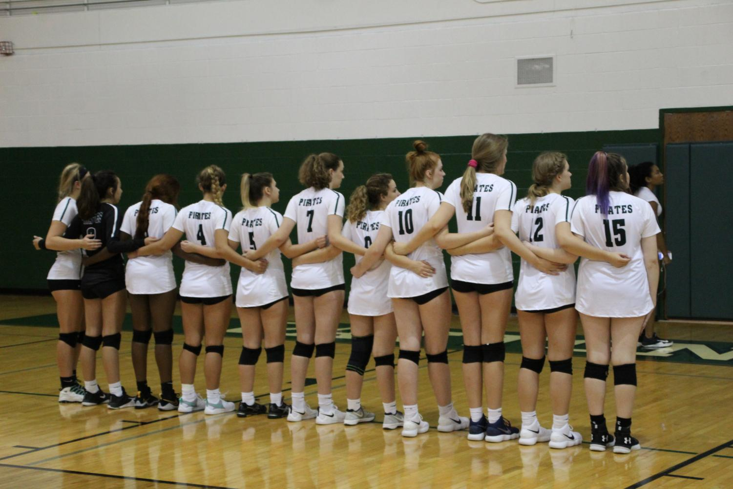 The volleyball team lines up for the singing of the National Anthem before a home match.