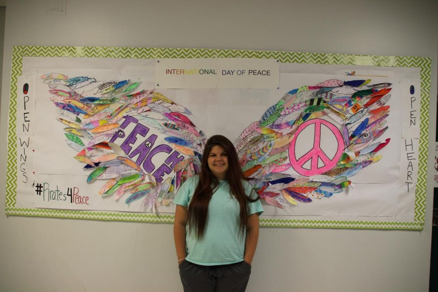 Kelsey+Hendricks+takes+a+photo+in+front+of+the+International+Club%27s+interactive+peace+wings+mural.+