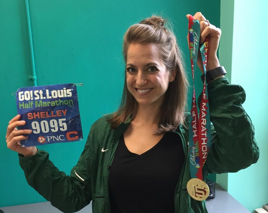 Ms. Shelley Christian holds her race bib and medal from the Go! St. Louis Half Marathon.