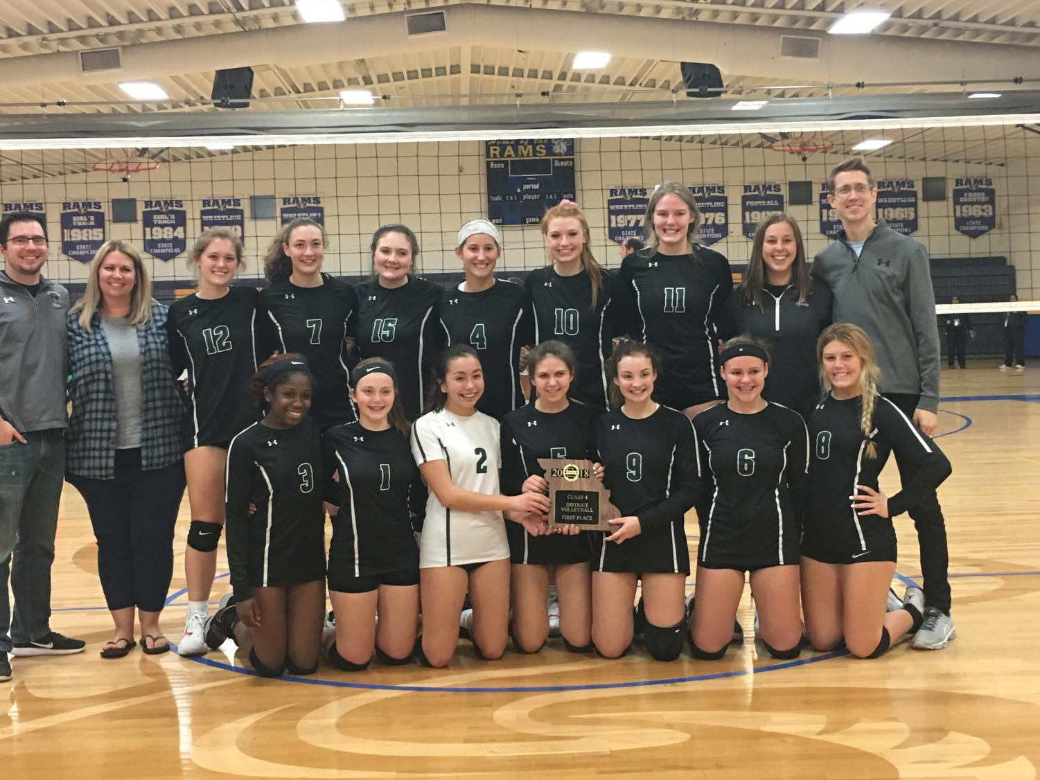 The girls' volleyball team holds the Class 4 District 5 championship trophy.