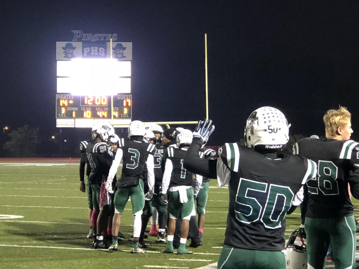 Pattonville players hold up four fingers to signal the start of the 4th quarter in the playoff game against Marquette High School.