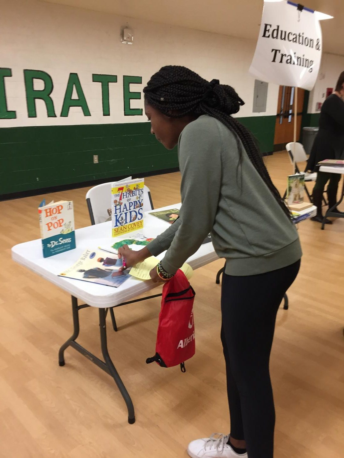 A student looks at materials available at the Career Fair table for those interested in becoming an educator.