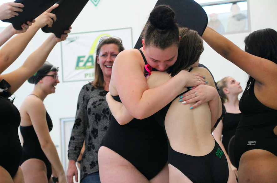 Allie+Fairbanks+hugs+a+teammate+when+walking+through+the+tunnel+with+her+parents+behind+her.+