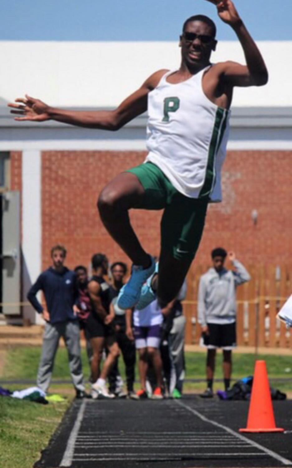Senior Michael Jackson competes in a jumping event during a track meet.