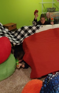 The Wright family building forts while they are under attack during a family-fun Nerf war.