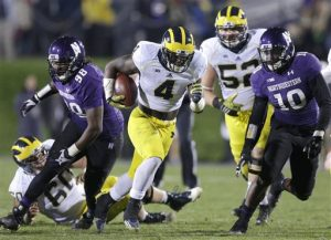 In this Nov. 8, 2014 file photo Michigan running back De'Veon Smith (4) runs against Northwestern during an NCAA college football game in Evanston, Ill. A Republican lawmaker in Michigan introduced a bill Dec. 2, 2014 to block collective bargaining for athletes that is on the fast track through this lame-duck legislative session, though there are no reports of such efforts at any of Michigan's public or private universities and opponents say it's a non-issue in their state. Athletes at Northwestern, a private school, voted in April to form the nation's first union for student athletes, a case the National Labor Relations Board has not yet ruled on. (AP Photo/Nam Y. Huh, File)