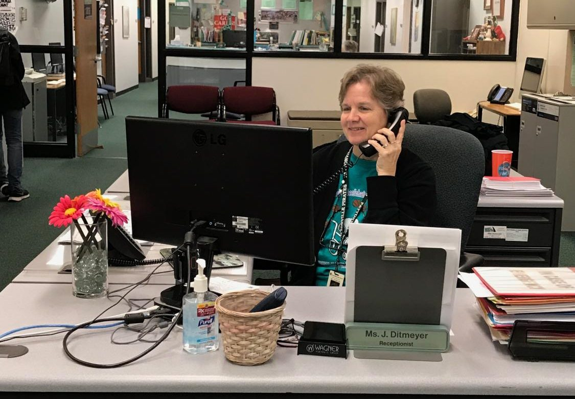 High school receptionist Ms. Jackie Ditmeyer takes a call from someone at her desk.