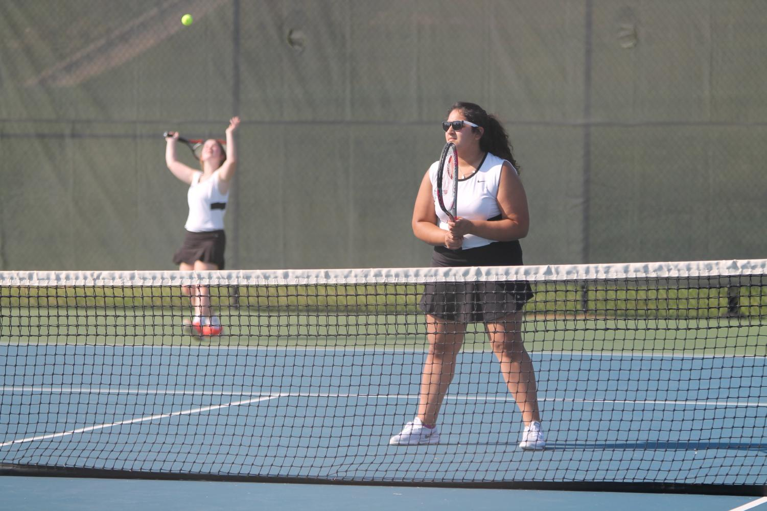 Aliza Ahmed (front) plays in a doubles match with her tennis partner.