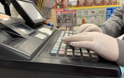 Cashier Megan Weeks wears protective gloves to help protect herself and the customers from the COVID-19 while she checks people out at Branneky Hardware.