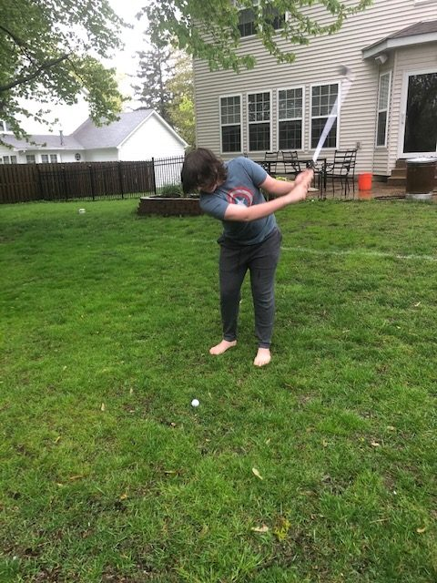 Practicing his swing in the yard, Thomas Clifford still finds a way to develop his skills.