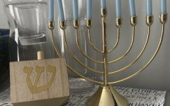A menorah with 9 candles in it for the 8 days of Hanukkah and one that is used to light the other candles, as well as a dreidel used to play a Jewish game.