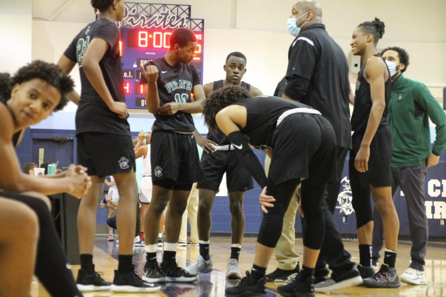 Varsity players Levi Banks, Kellen Thames, Alijah Carter, Justin Coleman, and Jonathan Cosby having timeout with head Coach Kelly Thames and assistant Coach Travis Harris  to see what their next play of action is. Sophomore Tory Allen has a  conversation with a fellow teammate.