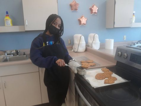 Lauren Turner places chocolate chip cookies on a cooling rack. Preparing recipes is one part of the Culinary Arts curriculum, but students also learned essential kitchen safety and kitchen management skills.