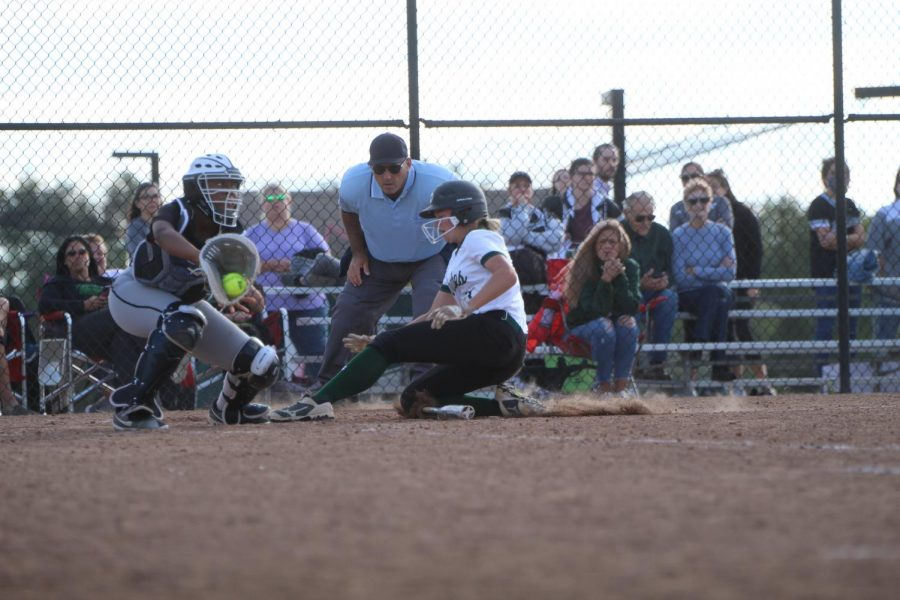 Pitcher Allison Schrumpf slides into home, rolling over the bat left from the last batter. She was declared safe, was wrapped up and went directly back to pitching consistent fastballs.