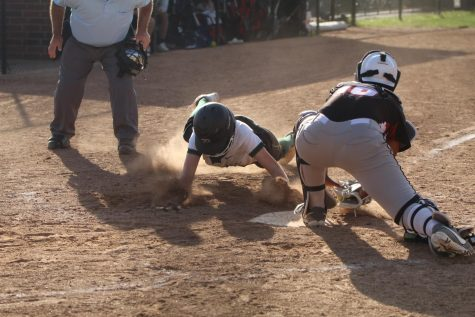 Madison Leckrone kicks up dirt, sliding in safe mere seconds before the catcher for the Wildcats can tag her out. The crowd was out of their seats in suspense.